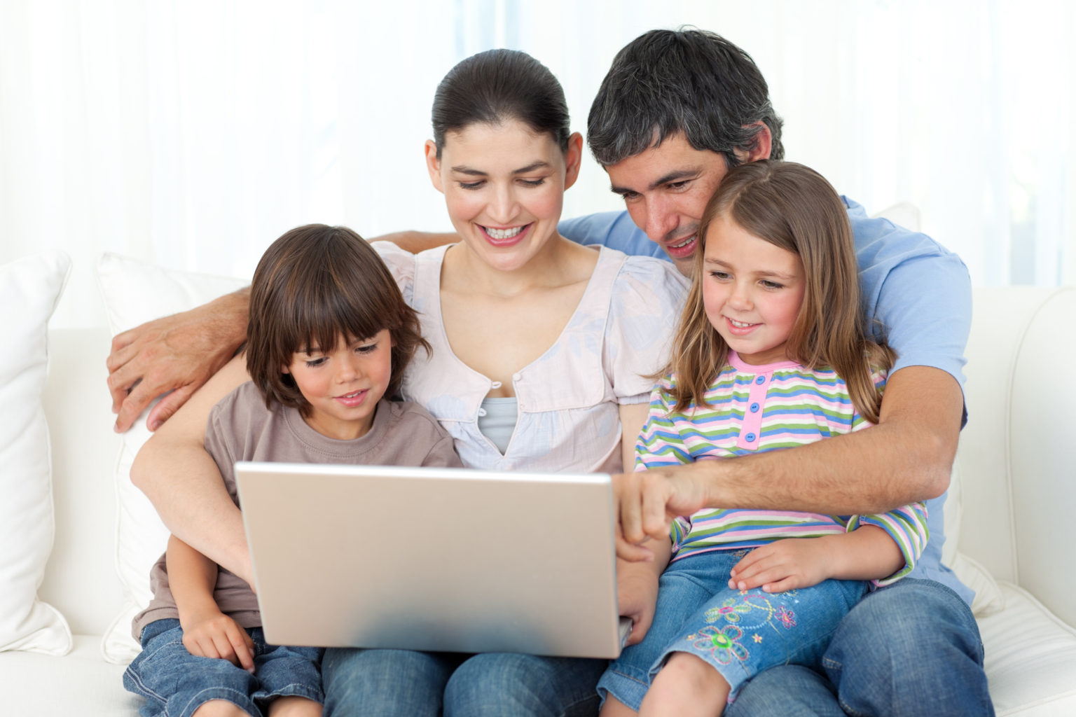 Jolly family using a laptop on the sofa at home